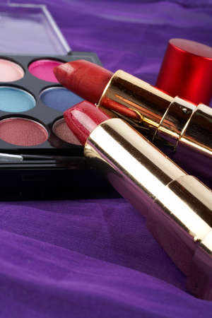 makeups: Detail of assortment of makeups.  Macro shot on malva background. Very shallow dof