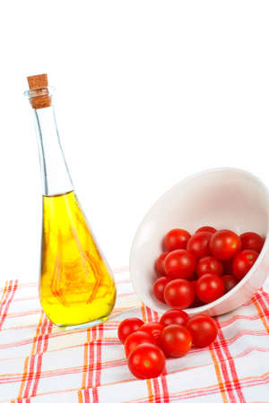 tomatos: Olive oil bottle and red tomatos cherry in the bowl