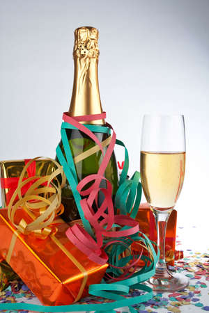 Assortment of gifts with champagne bottle and glass, ribbons and confetti on shadow background Stock Photo - 562549