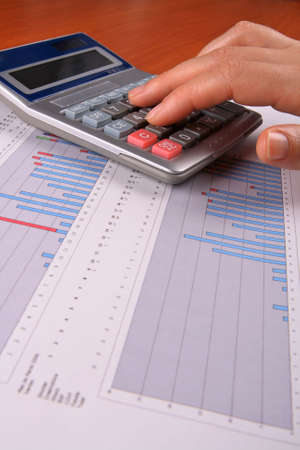 Business woman calculating over the stock chart photo