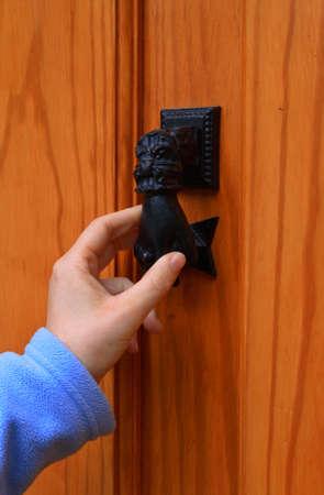 tocar la puerta: Una mujer llamando a la puerta de una casa  Foto de archivo