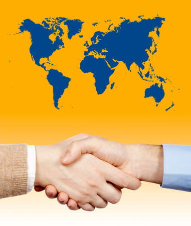 Business handshake under the world map over a gradient background photo