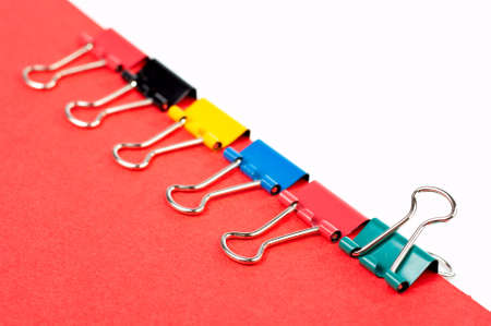 collate: Some colored paper clips binding a red document. Shallow DOF