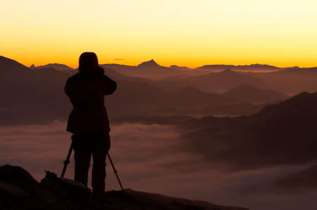 Silhouette of the photographer over the foggy mountain in a winter sunrise