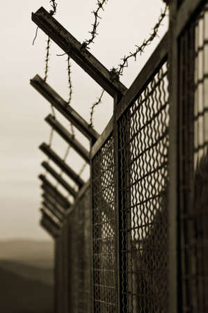 mesh fence: The security fence topped with barbed wire Stock Photo