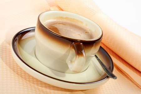 mingle: Close-up of a cup of coffee with the spoon, on ceramic plate