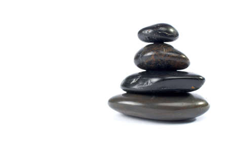 Stack of balanced stones with shadow on white background