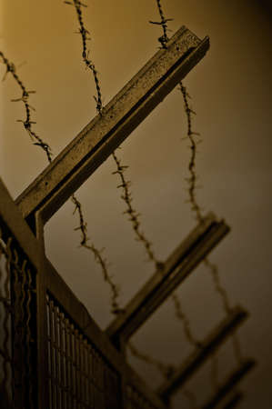 detain: The security fence topped with barbed wire. Shallow DOF. Duotone. Stock Photo