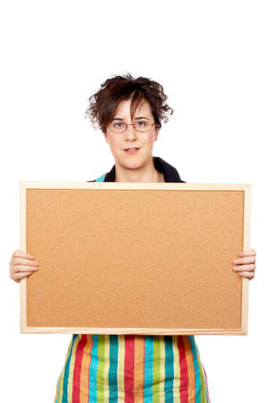Housewife in apron holding the empty corkboard on white background photo