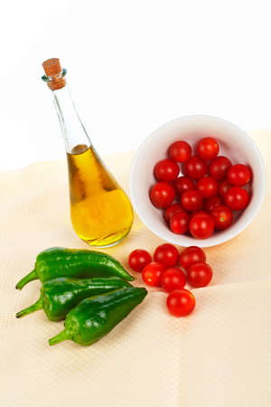 Olive oil bottle, red tomatos cherry in the bowl and green pepper Stock Photo - 728465