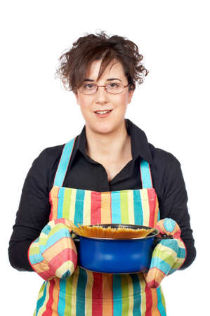Housewife in apron holding a blue pan with spaghetti uncooked inside