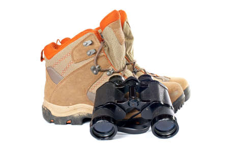 locality: Used hiking boots and binoculars with soft shadow on white background Stock Photo