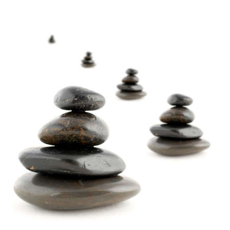 Stacks of balanced stones with shadow on white background. Very shallow DOF photo