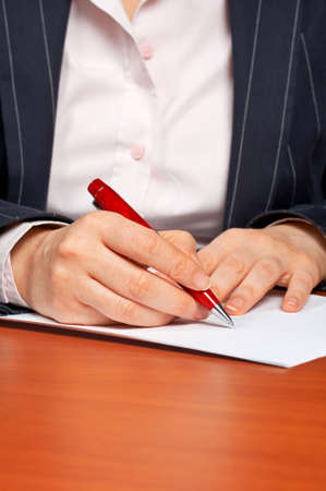 subscribing: Business woman writing a contract with focus on the hand in foreground Stock Photo