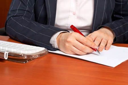 Business woman writing a contract with focus on the hand in foreground Stock Photo