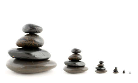 Stacks of balanced stones with shadow on white background. Very shallow DOF