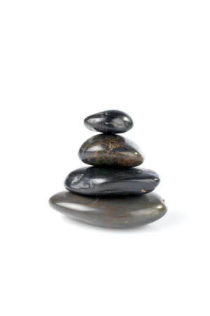 align: Stack of balanced stones with shadow on white background