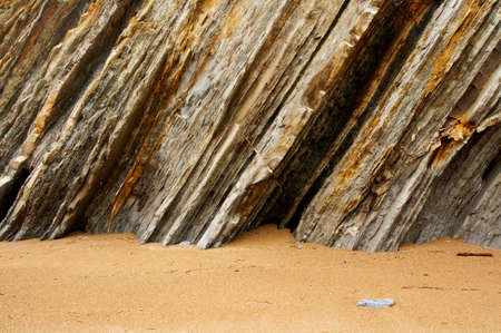 Multiple layers of eroded cliff in a beach photo