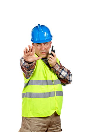 walkie: Construction worker with green safety vest worker talking with a walkie talkie and orders to stop. Hand on focus