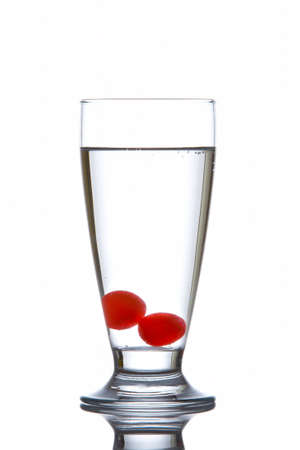 Glass of fresh water with cherries reflected on white background photo