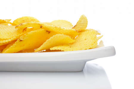 Potato chips on a plate reflected on white background