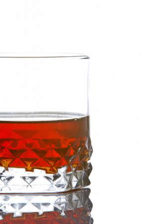 distilled: Un vetro del whisky ha riflesso su priorit� bassa bianca Archivio Fotografico