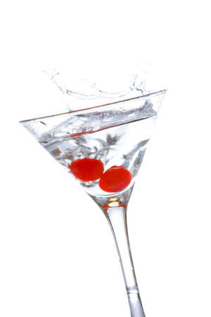 stirred: Two red cherrys splashing into a cocktail glass Stock Photo