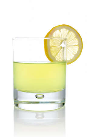 A glass of fresh lemon juice with a slice reflected on white background