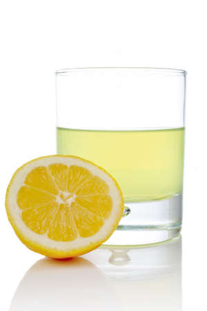 A half and glass of fresh lemon juice reflected on white background Stock Photo