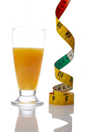 A glass of fresh orange juice and tape measure reflected on white background Stock Photo