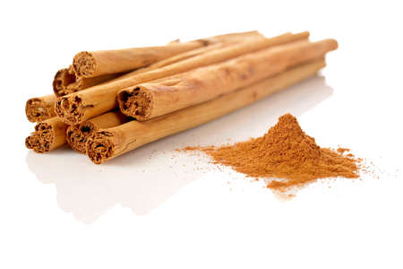 Sticks and powder of cinnamon reflected on the white background. Shallow DOF