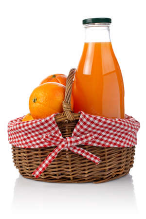 Three oranges and one bottle of fresh juice in a basket reflected on white background photo