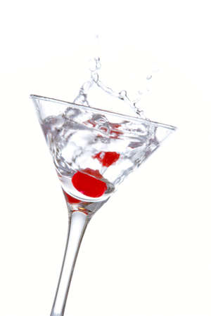 bartending: Two red cherrys splashing into a cocktail glass Stock Photo