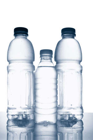 Three bottles of mineral water with droplets reflecting on white background Stock Photo