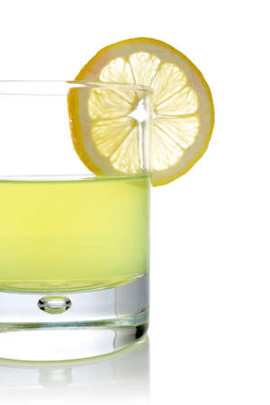A glass of fresh lemon juice with a slice reflected on white background photo