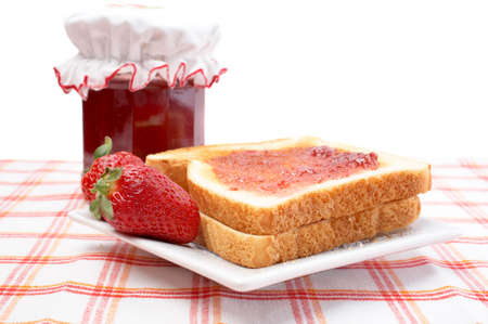 Two strawberries and toasts in a dish, in front of jam jar. Shallow DOF photo