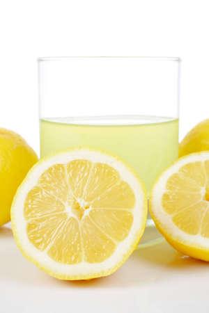 A glass of fresh lemon juice reflected on white background. Shallow DOF photo