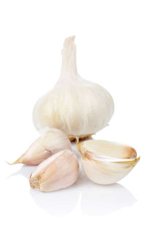 nutriments: Garlic and cloves reflected on white background. Shallow DOF