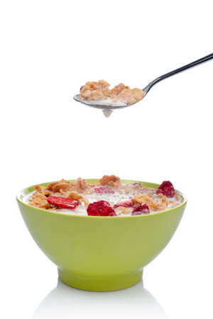 Cornflakes with fruits on the spoon above the green bowl. Shallow DOF photo