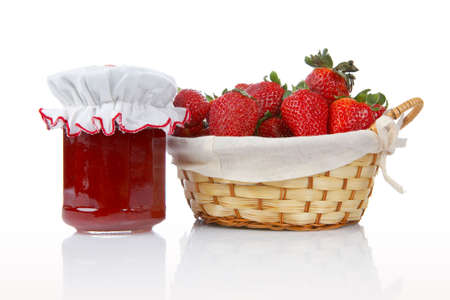 Jam jar and basket of strawberries reflected on white background photo