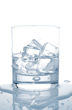 Glass of fresh mineral water with ice cubes reflected on wet background Banco de Imagens - 956575