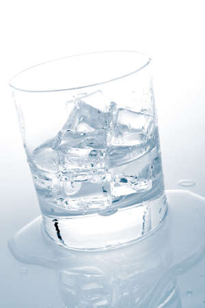 insipid: Glass of fresh mineral water with ice cubes reflected on wet background