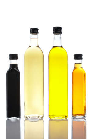 Several bottles of olive oil and vinegar reflected on white background Banco de Imagens - 1016574
