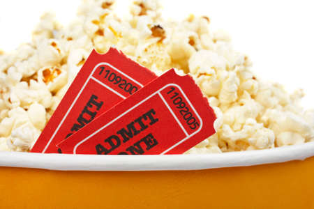 edibles: Detail of popcorn in a bucket and two tickets over a white background. Tickets on focus and shallow DOF