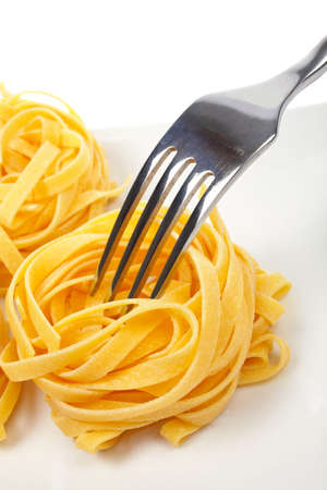 A uncooked pasta nests and fork on a dish on white background photo