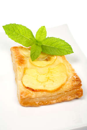 Fresh apple tart with leaves of mint on a dish, isolated on white background