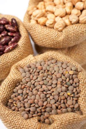 렌즈 콩: Burlap sack with lentils over a white background. Shallow DOF