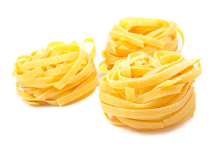 starch: Three uncooked pasta nests with soft shadow on white background