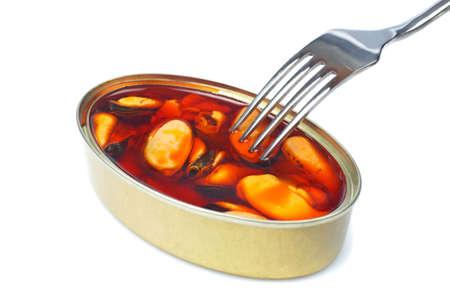 plato del buen comer: El tenedor por encima de los mejillones en conserva con suave sombra sobre fondo blanco