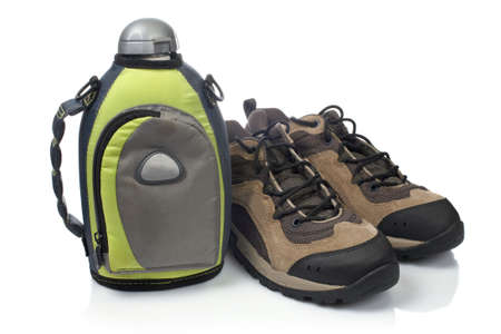 water shoes: A pair of hiking boots and canteen with shadow, reflected on white background